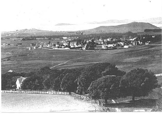 """A photographic view from the northwestern edge of Thomas' La Loma property. In addition to seeing a portion of the fence around Thomas' ranch, one can see the look of the northern settlements and industry. Fleming Point, Brooks Island and Albany Hill are seen at the top of the photograph.  If you look closely at Fleming Point, you can see the wharf of the dynamite plant and the smoke stacks of the acid recovery system of the chemical operation. The Peralta Park Hotel, with its towers, is nestled in the upper middle of the photo between Albany hill to the north and Flemming Point to the south. The hotel asserted itself on the horizon by about 1889, dating the photo's earliest possible date. The enclave of North Berkeley, centered around Berryman Station rail stop of Southern Pacific at Shattuck Avenue and Vine Street is seen at the mid-right. From the book """"Eccentrics, Heroes, and Cutthroats"""" by Richard Schwartz. Photo: Courtesy Richard Schwartz"""