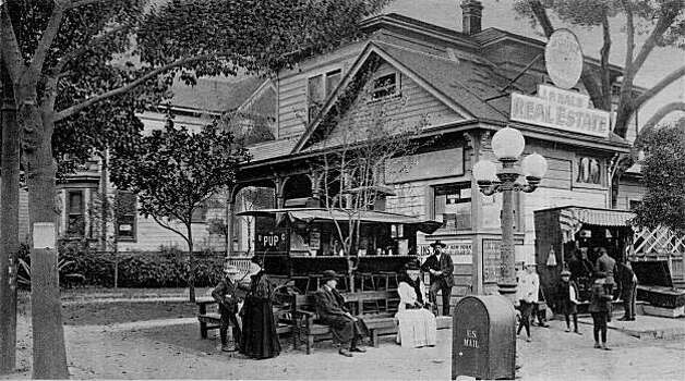 """Bill Henderson was one of Berkeley's most eccentric and favorite street vendors.  People would travel far to revisit their old stool at Bill's hot dog stand long after graduation. In this photo, Bill Henderson, circa 1906, is putting together one of his famous """"dog sandwiches."""" This photo is a version of one of the famous outdoor dogcarts operated at various locations around Berkeley. Note that Bill's neighbor is the realtor J. P. Hale, who changed from being a cabinetmaker to a realtor and bicycle salesman in 1902, keeping his same address of 1504 Shattuck Avenue. That would be around Shattuck Avenue and Vine. This postcard is dated 1906 and, by then, Hale had an office at 1511 Shattuck Avenue and a branch at 2515 Shattuck Avenue, near Shattuck and Dwight Way. The 1907 city directory places Hale at the northwest corner of University and Shattuck Avenues. It is known that Bill the Hot Dog Man did have a cart at this location and it seems likely that this indeed is the location of this image.  Bill would attract high school and college students, and many graduates at his stand. Bill would often close down his stand if one of his patrons would tell him of some exotic or fun California place and Bill would run to visit the location, looking for adventure.  From the book """"Eccentrics, Heroes, and Cutthroats"""" by Richard Schwartz. Photo: Courtesy Richard Schwartz"""