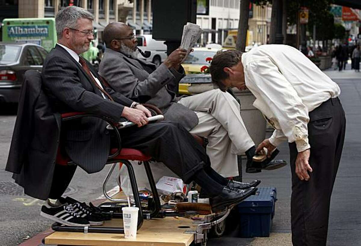 Bruce McCoy (left) has his shoes shined by Larry Moore while another customer Anthony Garner (center) waits his turn at Market and New Montgomery streets in San Francisco, Calif., on Thursday, June 4, 2009.