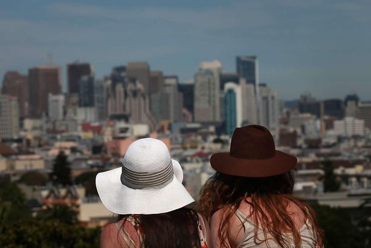 Lynn Chuba and Lucia Znamirowski, both of San Francisco, take cover from the sun under their hats as they take in the view from Dolores Park on Wednesday, March 30, 2011 in San Francisco, Calif.