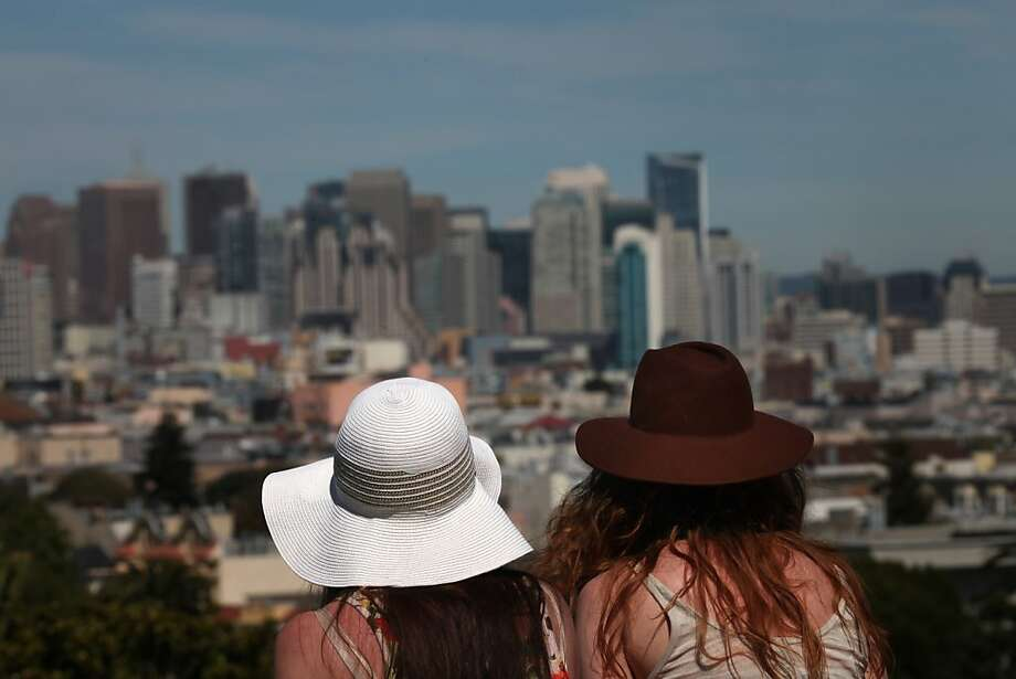Lynn Chuba and Lucia Znamirowski, both of San Francisco, take cover  from the sun under their hats as they take in the view from Dolores Park on Wednesday, March 30, 2011 in San Francisco, Calif. Photo: Lea Suzuki, The Chronicle