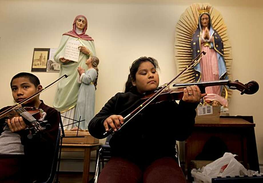 Violin class for 4th graders Anthony and Areli, on Wednesday Dec. 1 , 2010, at the De Marillac Academy, which in San Francisco, Calif. Practicing below statues of St. Anne and Mary. Photo: Michael Macor, The Chronicle