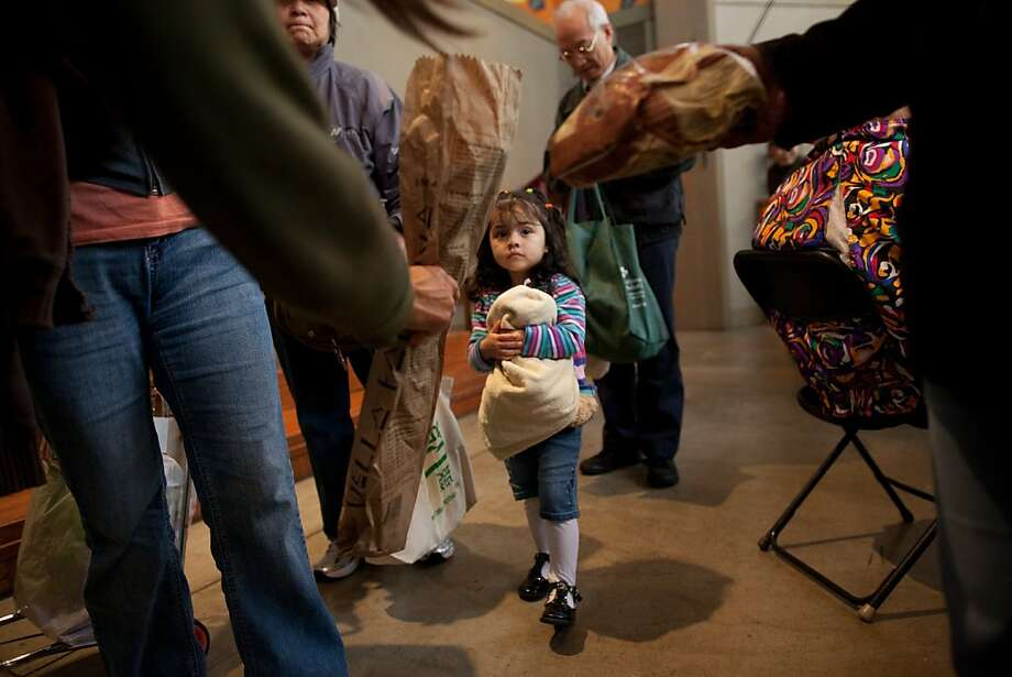 Naomi Lopez, 2 goes through the food line with her mother Elizabeth Navarro during a Food Pantry food giveaway at the Saint Gregory of Nyssa Episcopal Church on March 25, 2011 in San Francisco, Calif. Photograph by David Paul Morris/Special to the Chronicle Photo: David Paul Morris, Special To The Chronicle