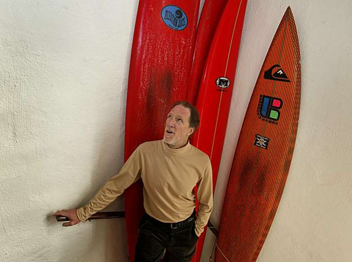 Dr. Mark Renneker stops in the hallway of his home, which is also a display area for his many surfboards Wednesday November 24, 2010. Mark Renneker, M.D. is the famous surfing doctor of Ocean Beach in San Francisco, Calif.