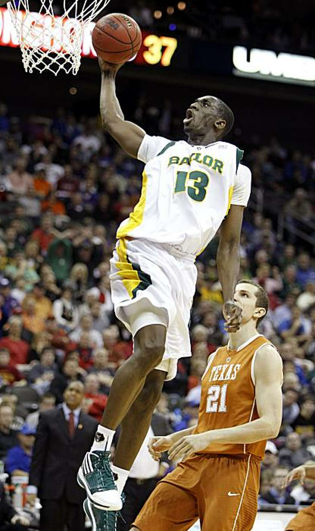 This March 11 photo shows Baylor center Ekpe Udoh (13) shooting over Texas center Matt Hill during the first half of an NCAA college basketball game at the Big 12 Conference men's tournament in Kansas City, Mo.