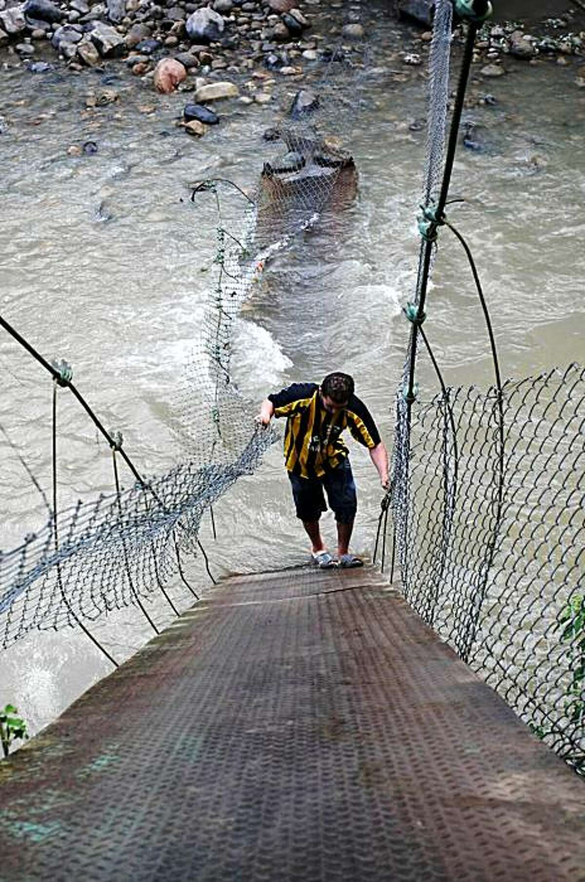 A man climbs a fallen footbridge that links Colombia and Venezuela over the Tachira River in Ragonvalia in northeastern Colombia, Friday, Nov. 20, 2009. Venezuelan Vice President Ramon Carrizales said Venezuelan soldiers destroyed two make shift bridges along its border with Colombia on Nov. 19 because they were being used by drug traffickers.