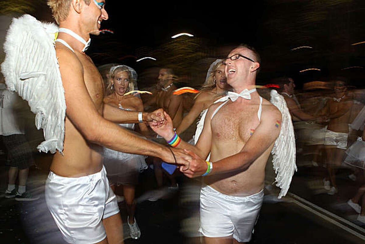 SYDNEY, AUSTRALIA - MARCH 05: Parade goers dance during the 2011 Sydney Gay & Lesbian Mardi Gras Parade on March 5, 2011 in Sydney, Australia.