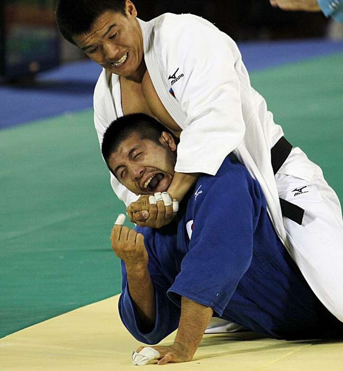 Japan's Masahiro Takamatsu bottom, reacts as he is held by Mongolia's Uuganbaatar Otgonbaatar during a bronze medal match for the judo -81kg competitions at the 16th Asian Games in Guangzhou, China, Sunday, Nov. 14, 2010.