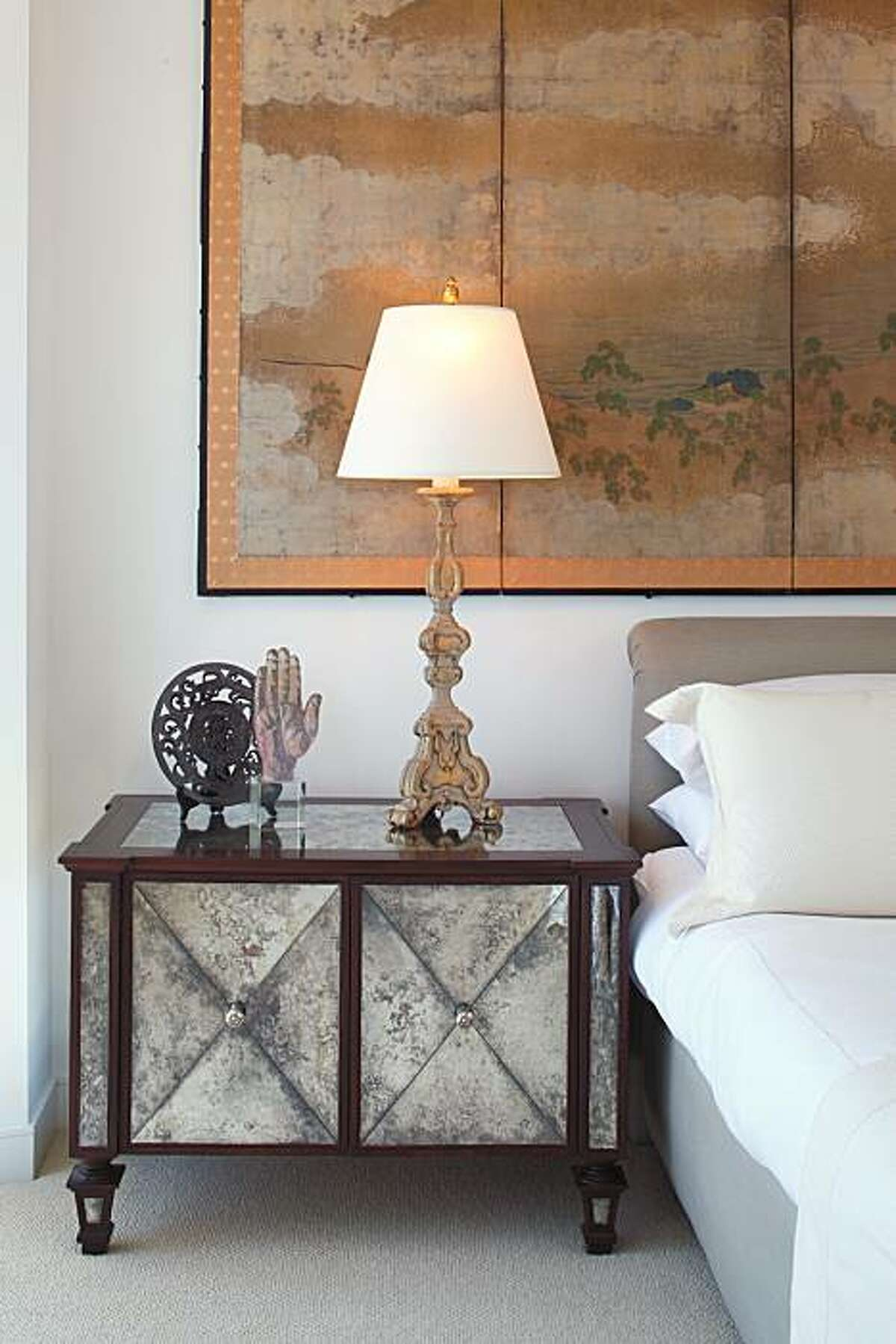A six-panel Edo-era Japanese screen now hangs above the couple's bed. Two walnut and antique-mirror side tables that Turner designed now flank the bed as nightstands.
