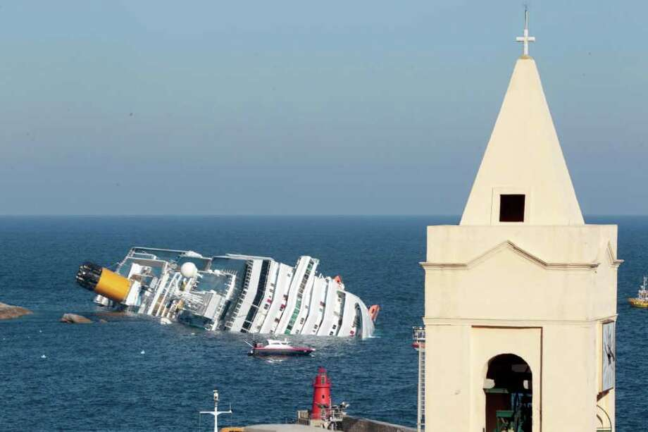 The luxury cruise ship Costa Concordia leans on its starboard side after running aground off the port at Giglio, on the tiny Tuscan island of Giglio, Italy, Saturday, Jan. 14, 2012.  The luxury cruise ship ran aground off the coast of Tuscany, sending water pouring in through a 160-foot (50-meter) gash in the hull and forcing the evacuation of some 4,200 people from the listing vessel early Saturday, the Italian coast guard said.  The number of dead and injured is not yet confirmed Coast Guard Cmdr. Francesco Paolillo said. Photo: Gregorio Borgia, AP / AP