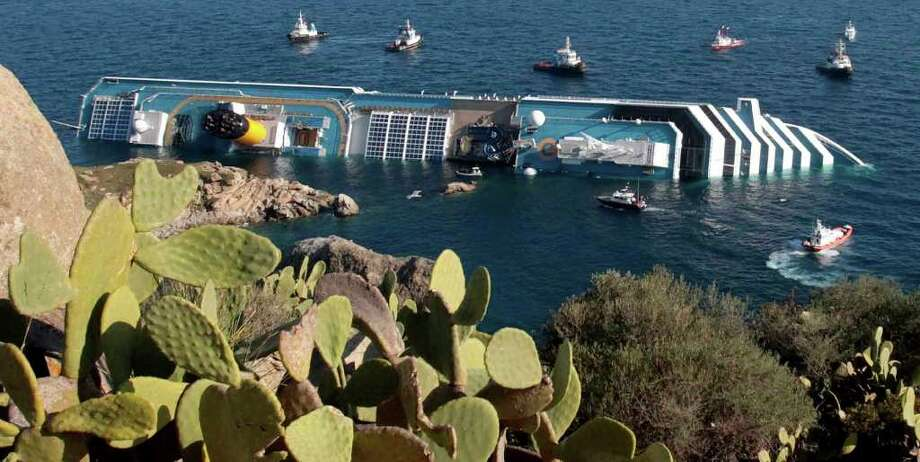 Rescue boats approach the luxury cruise ship Costa Concordia resting on its starboard side after running aground near the tiny Tuscan island of Isola del Giglio, Italy, Saturday, Jan. 14, 2012.  The luxury cruise ship ran aground off the coast of Tuscany, sending water pouring in through a 160-foot (50-meter) gash in the hull and forcing the evacuation of some 4,200 people from the listing vessel early Saturday, the Italian coast guard said.  In the background Italy's mainland. Photo: Gregorio Borgia, AP / AP