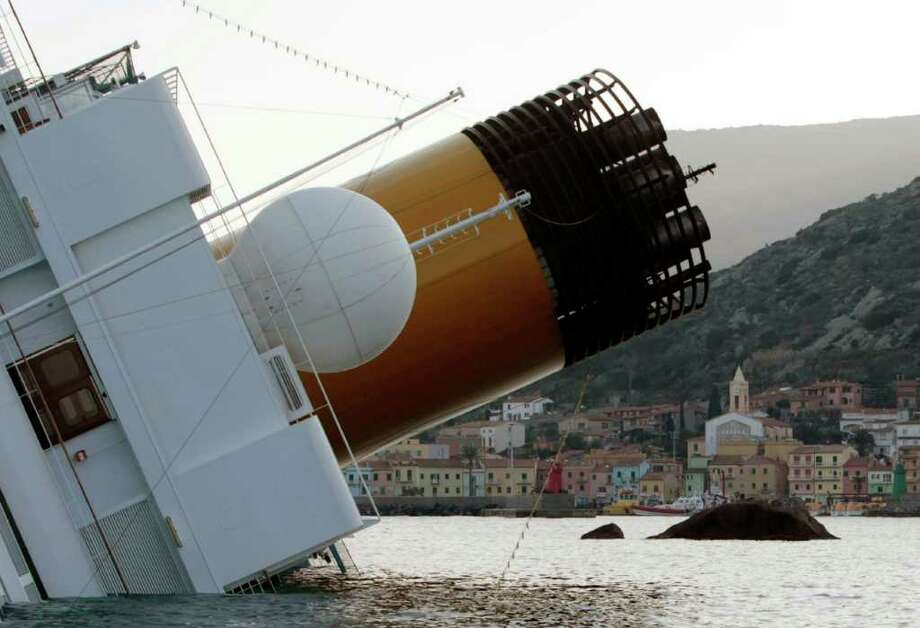 The luxury cruise ship Costa Concordia leans on its side after running aground the tiny Tuscan island of Giglio, Italy, Saturday, Jan. 14, 2012. A luxury cruise ship ran aground off the coast of Tuscany, sending water pouring in through a 160-foot (50-meter) gash in the hull and forcing the evacuation of some 4,200 people from the listing vessel early Saturday, the Italian coast guard said. Photo: Gregorio Borgia, AP / AP