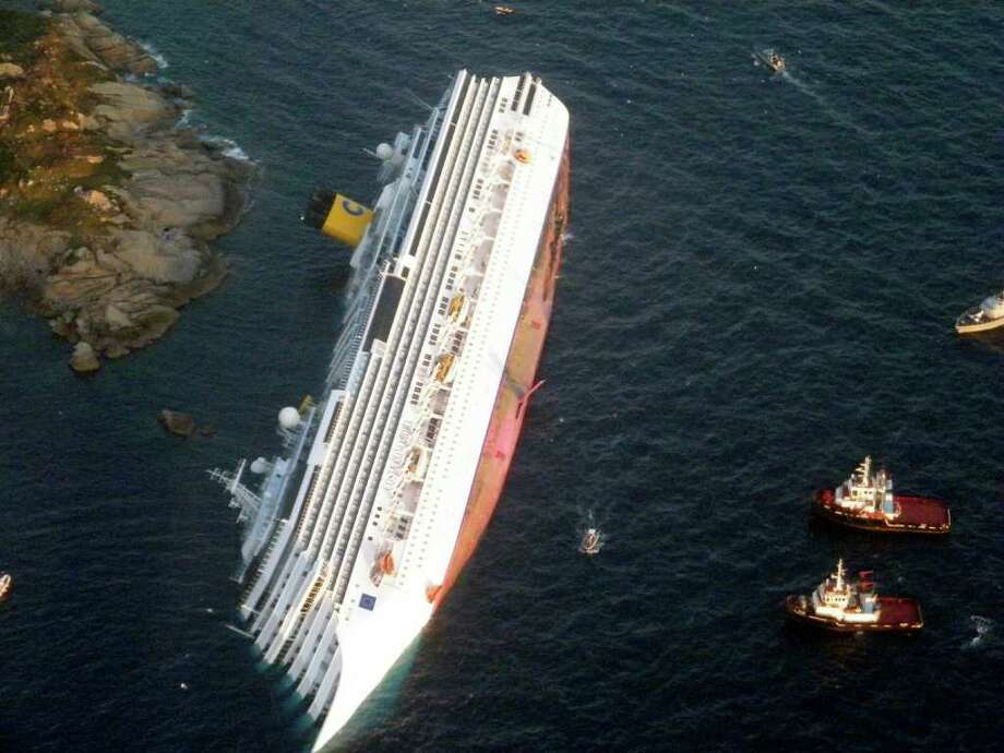 In this photo released by the Guardia di Finanza (Border Police), the luxury cruise ship Costa Concordia leans on its side after running aground off the tiny Tuscan island of Giglio, Italy, Saturday, Jan. 14, 2012. The luxury cruise ship ran aground off the coast of Tuscany, sending water pouring in through a 160-foot (50-meter) gash in the hull and forcing the evacuation of some 4,200 people from the listing vessel early Saturday, the Italian coast guard said. Photo: AP / Guardia Di Finanza