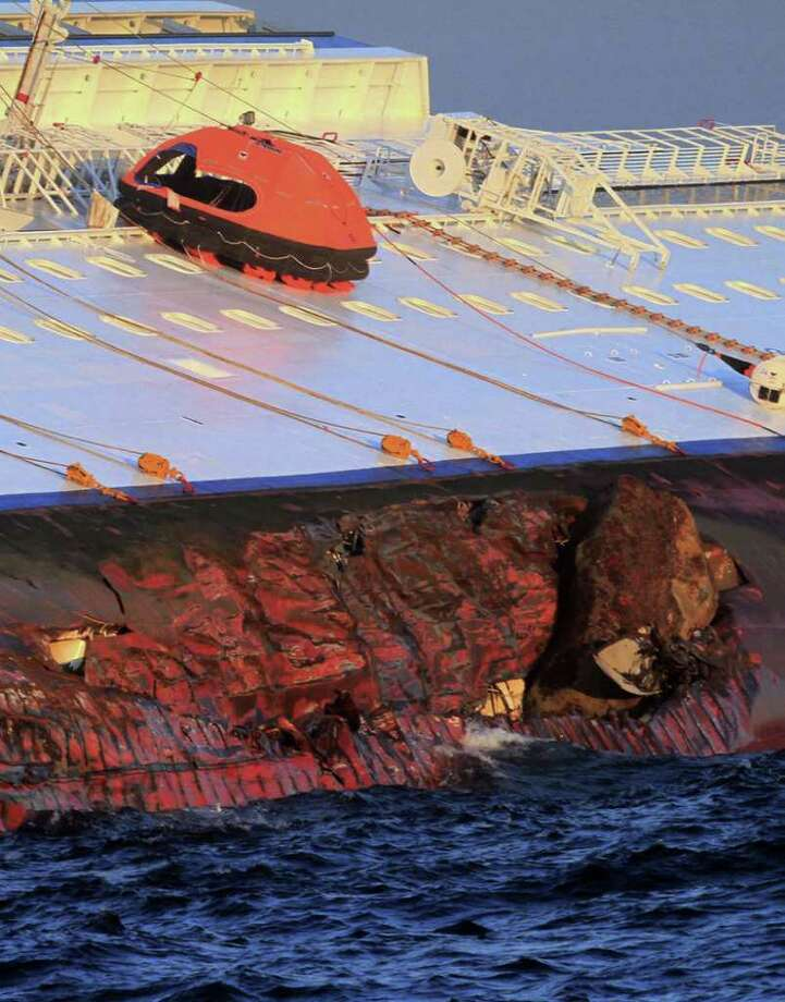 The luxury cruise ship Costa Concordia leans on its side as after running aground off the tiny Tuscan island of Giglio, Italy, Saturday, Jan. 14, 2012. The luxury cruise ship ran aground off the coast of Tuscany, sending water pouring in through a 160-foot (50-meter) gash in the hull and forcing the evacuation of some 4,200 people from the listing vessel early Saturday, the Italian coast guard said. Photo: Enzo Russo, AP / AP
