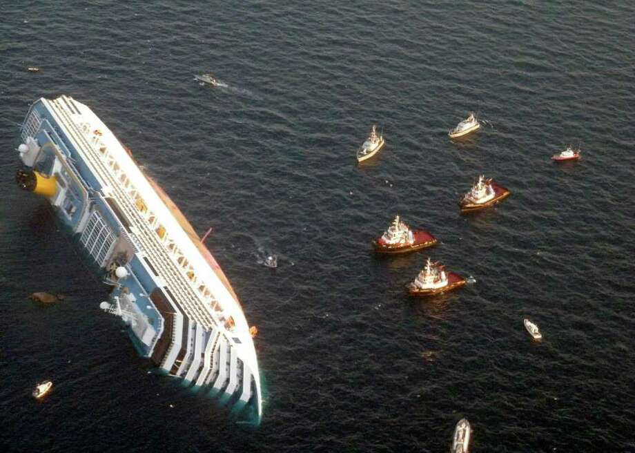 In this photo released by the Guardia di Finanza (border Police), the luxury cruise ship Costa Concordia leans on its side after running aground off the tiny Tuscan island of Giglio, Italy, Saturday, Jan. 14, 2012.  The luxury cruise ship ran aground off the coast of Tuscany, sending water pouring in through a 160-foot (50-meter) gash in the hull and forcing the evacuation of some 4,200 people from the listing vessel early Saturday, the Italian coast guard said.  The number of dead and injured is not yet confirmed Coast Guard Cmdr. Francesco Paolillo said. Photo: AP / Guardia Di Finanza