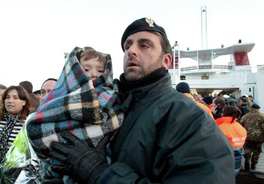A police officer holds a baby wrapped in a blanket as passengers of the luxury ship Costa Concordia