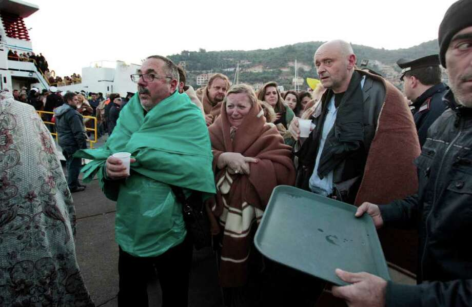 Passengers of the luxury ship that ran aground off the coast of Tuscany arrive on a ferry in Porto Santo Stefano, Italy, Saturday, Jan. 14, 2012. A luxury cruise ship ran aground off the coast of Tuscany, gashing open the hull and taking on water, forcing some 4,200 people aboard to evacuate aboard lifeboats to a nearby island early Saturday. At least three were dead, the Italian coast guard said. Three bodies were recovered from the sea, said Coast Guard Cmdr. Francesco Paolillo. Photo: Gregorio Borgia, AP / AP