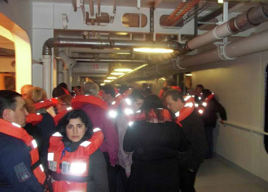 This photo acquired by the Associated Press from a passenger of the luxury ship that ran aground off the coast of Tuscany shows fellow passengers wearing life-vests on board the Costa Concordia  as they wait to be evacuated, Saturday, Jan. 14, 2012. A luxury cruise ship ran aground off the coast of Tuscany, sending water pouring in through a 160-foot (50-meter) gash in the hull and forcing the evacuation of some 4,200 people from the listing vessel early Saturday, the Italian coast guard said. Photo: AP / AP