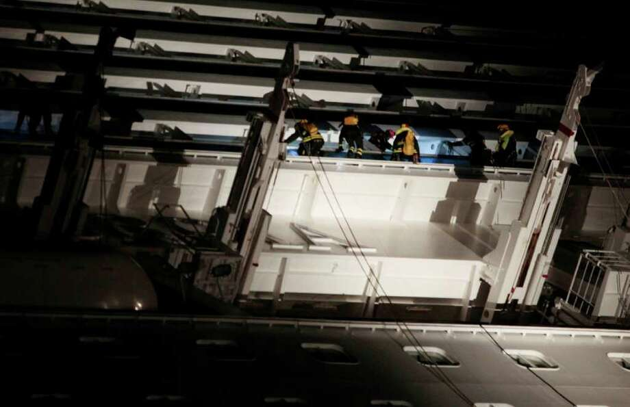 italian firefighters climb on the luxury cruise ship Costa Concordia leaning on its side after running aground the tiny Tuscan island of Giglio, Italy, Saturday, Jan. 14, 2012. The ship ran aground off the coast of Tuscany, sending water pouring in through a 160-foot (50-meter) gash in the hull and forcing the evacuation of some 4,200 people from the listing vessel early Saturday, the Italian coast guard said. Photo: Gregorio Borgia, AP / AP