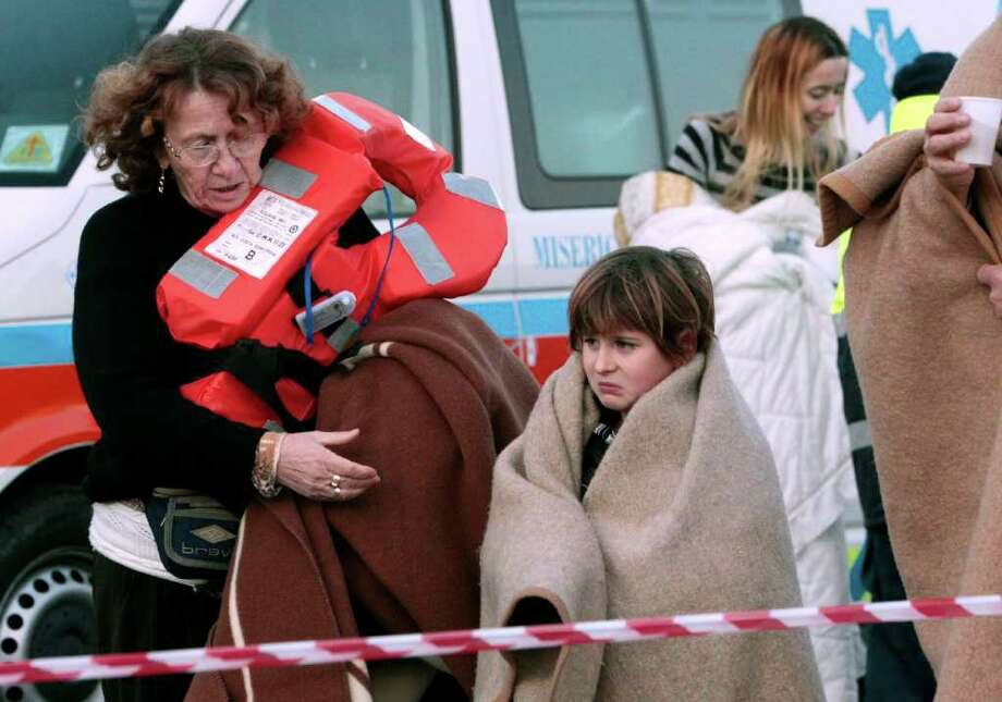 Passengers of the luxury ship that ran aground off the coast of Tuscany disembark a ferry in Porto Santo Stefano, Italy, Saturday, Jan. 14, 2012. A luxury cruise ship ran aground off the coast of Tuscany, gashing open the hull and taking on water, forcing some 4,200 people aboard to evacuate aboard lifeboats to a nearby island early Saturday. At least three were dead, the Italian coast guard said. Three bodies were recovered from the sea, said Coast Guard Cmdr. Francesco Paolillo. Photo: Gregorio Borgia, AP / AP
