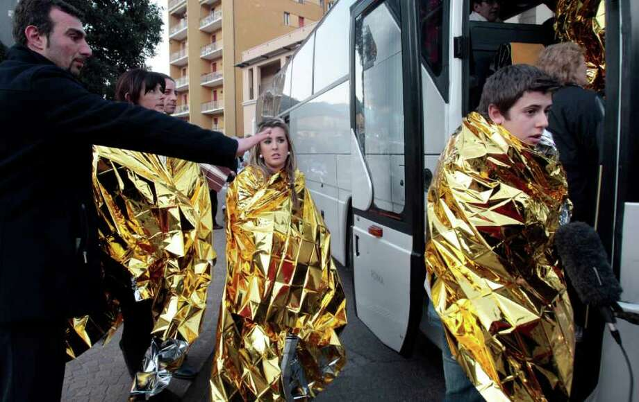 Passengers of the luxury ship that ran aground off the coast of Tuscany board a bus in Porto Santo Stefano, Italy, Saturday, Jan. 14, 2012. A luxury cruise ship ran aground off the coast of Tuscany, gashing open the hull and taking on water, forcing some 4,200 people aboard to evacuate aboard lifeboats to a nearby island early Saturday. At least three were dead, the Italian coast guard said. Three bodies were recovered from the sea, said Coast Guard Cmdr. Francesco Paolillo. Photo: Gregorio Borgia, AP / AP