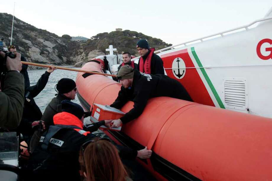 Italian Coast guard personnel pass on the black box of the luxury cruise ship Costa Concordia after running aground the tiny Tuscan island of Giglio, Italy, Saturday, Jan. 14, 2012. A luxury cruise ship ran aground off the coast of Tuscany, sending water pouring in through a 160-foot (50-meter) gash in the hull and forcing the evacuation of some 4,200 people from the listing vessel early Saturday, the Italian coast guard said. Photo: Gregorio Borgia, AP / AP