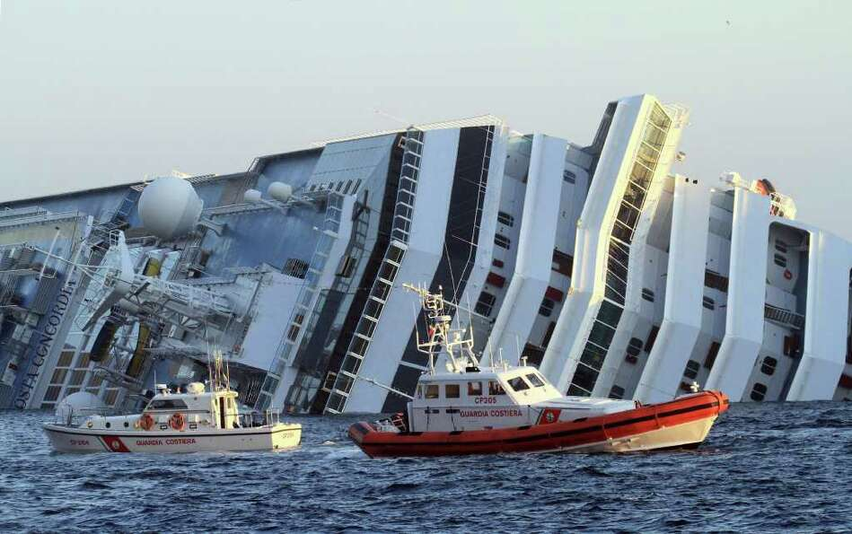 The luxury cruise ship Costa Concordia leans on its side as after running aground off the tiny Tusca