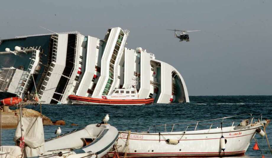 The luxury cruise ship Costa Concordia leans on its side as a helicopter flies past, after the ship ran aground of the port of Griglio, on the tiny Tuscan island of Giglio, Italy, Saturday, Jan. 14, 2012. The luxury cruise ship ran aground off the coast of Tuscany, sending water pouring in through a 160-foot (50-meter) gash in the hull and forcing the evacuation of some 4,200 people from the listing vessel early Saturday, the Italian coast guard said.  The number of dead and injured is not yet confirmed Coast Guard Cmdr. Francesco Paolillo said. Photo: Gregorio Borgia, AP / AP