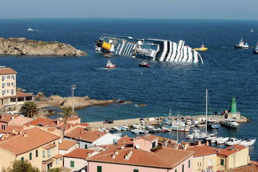 The luxury cruise ship Costa Concordia leans on its starboard side off the port at Giglio after runn
