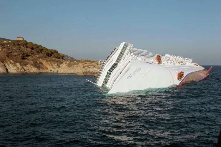 A luxury cruise ship Costa Concordia leans on its side after running aground the tiny Tuscan island of Giglio, Italy, Saturday, Jan. 14, 2012. A luxury cruise ship ran aground off the coast of Tuscany, sending water pouring in through a 160-foot (50-meter) gash in the hull and forcing the evacuation of some 4,200 people from the listing vessel early Saturday, the Italian coast guard said. Photo: Gregorio Borgia, AP / AP