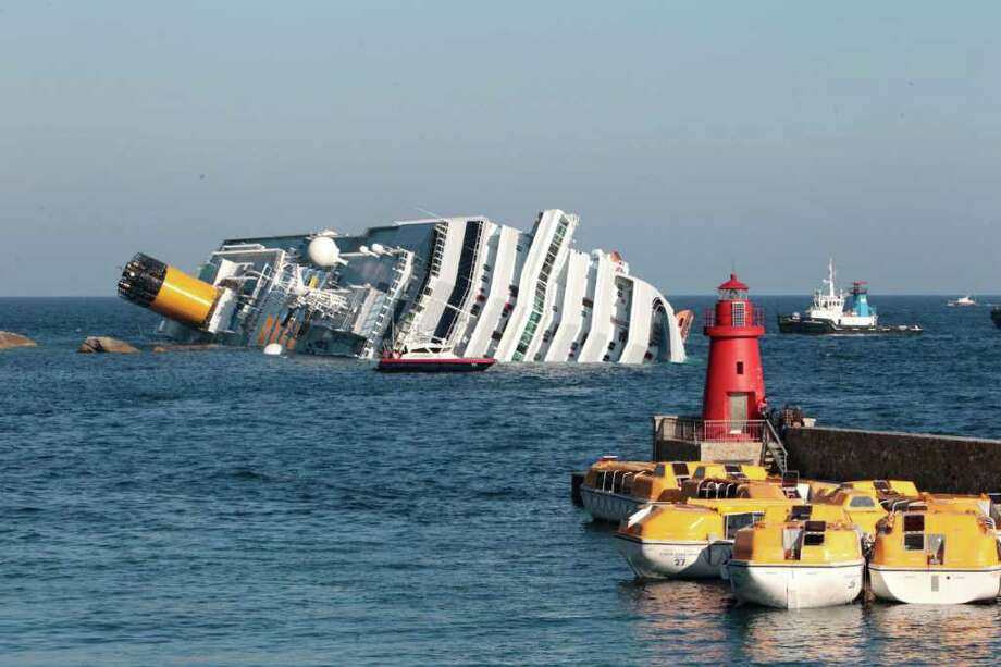 A luxury ship Costa Concordia leans on the rocks after running aground the tiny Tuscan island of Giglio, Saturday, Jan. 14, 2012. A luxury cruise ship ran aground off the coast of Tuscany, sending water pouring in through a 160-foot (50-meter) gash in the hull and forcing the evacuation of some 4,200 people from the listing vessel early Saturday, the Italian coast guard said. Photo: Gregorio Borgia, AP / AP