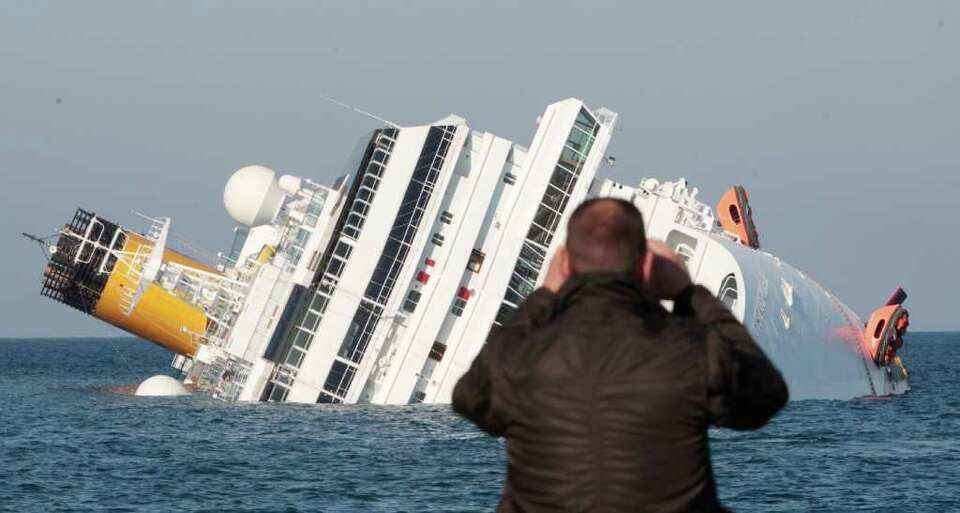 The luxury cruise ship Costa Concordia leans on its side after running aground off the tiny Tuscan i