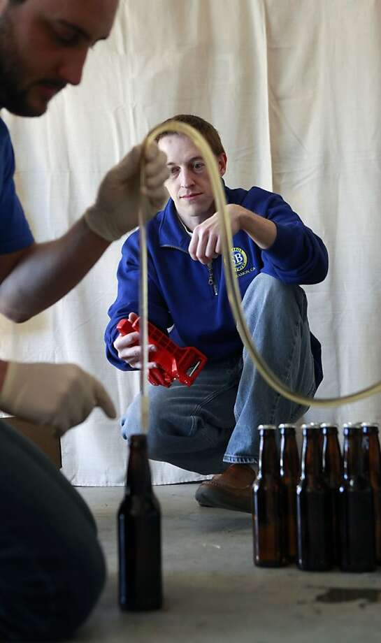 Schubros Brewery President Ian Schuster rear waits to cap bottles while Brew Master Mike Johannsen pours, Nico American Wheat in their San Ramon California test kitchen Thursday, January 12, 2012. Photo: Lance Iversen, The Chronicle