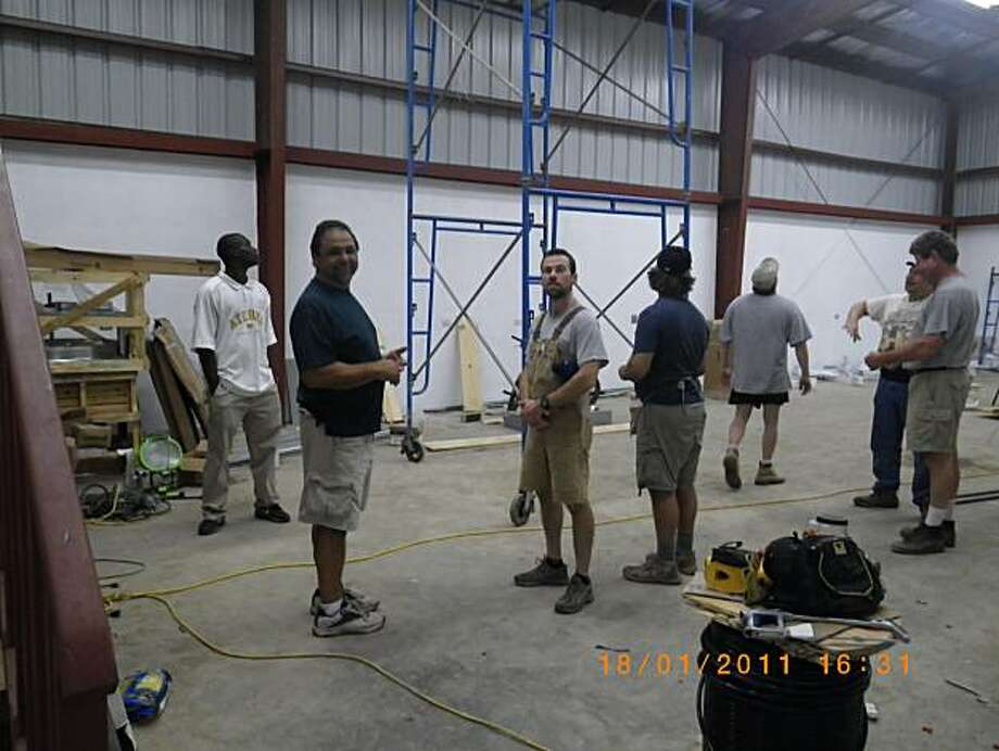 Lewis, a Haitian electrician/translator, Jeff Rodriguez, a volunteer electrician/foreman, Justin Connolly, a volunteer electrician, Tom Cooper, a volunteer electrician/project manager, Bob Plante, a volunteer electrician, AT&T Technician, Dr. Bob Bartolone, volunteer physician/electrician apprentice and Bill Donohoe, a volunteer electrician have a meeting to plan  lighting, fan and wiring for Sacred Heart Hospital in the northern Haitian town of Milot. Photo: Walt Vernon, Special To The Chronicle