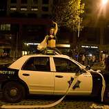 A woman dances on top of a San Francisco police car as Giants fans celebrate the World Series win on King Street between 3rd and 4th Street in San Francisco, Calif., on Monday, November 1, 2010