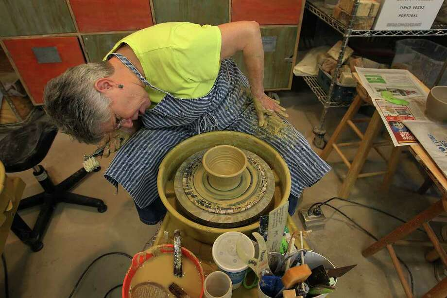 Janan Moses contorts herself in order to see various angles of her bowl on a throwing wheel. Moses joined other members of the San Antonio Potters Guild at Southwest School of Art for the Empty Bowls Bowl-a-Thon to benefit SAMMinistries on Saturday, Jan. 14, 2012. Photo: KIN MAN HUI, SAN ANTONIO EXPRESS-NEWS / San Antonio Express-News