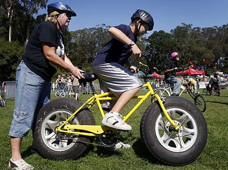 Janet Parcells helps her son Todd ride a bicycle built with automobile tires at the Tour de Fat bicycle parade and festival at Golden Gate Park in San Francisco on Saturday. After a ride through the park, bicyclists were entertained by musicians, played bicycle games and got their bikes tuned up for free. The event was hosted by a beer manufacturer and the San Francisco Bike Coalition. Photo: Paul Chinn, The Chronicle