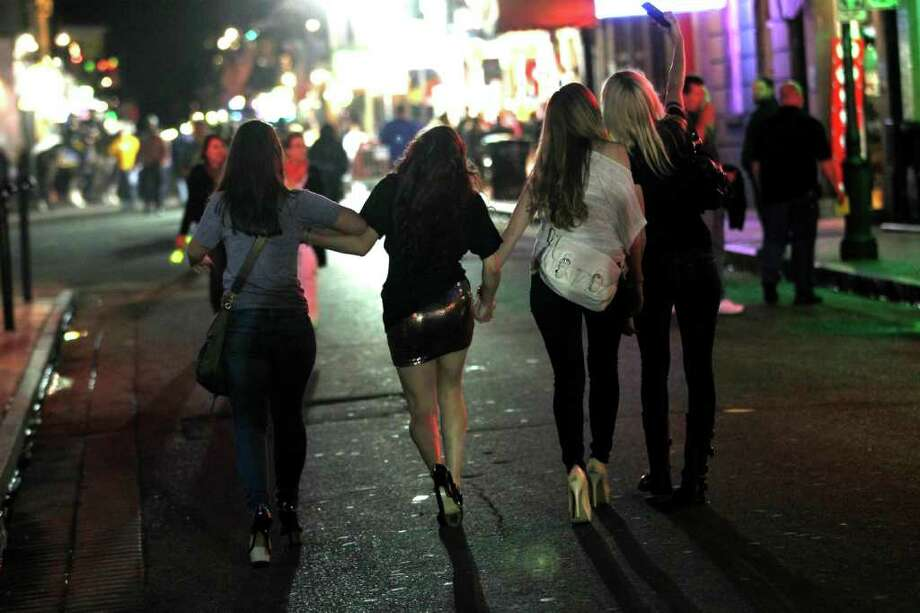 Revelers walk down Bourbon Street in the French Quarter last week. Youths 16 and under will have to be off the streets by 8 p.m. on weekends under the curfew. Photo: Gerald Herbert / AP