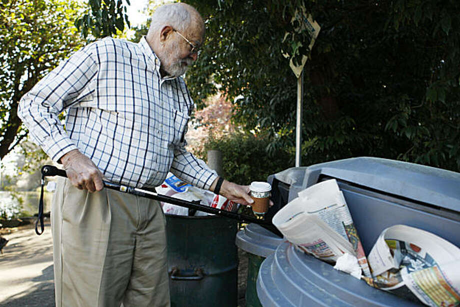 Robert Laws of San Francisco uses his cane to open the only trash can that is not overflowing with trash near Stow Lake in Golden Gate Park on Saturday, Feb. 12, 2011. Photo: Alex Washburn, The Chronicle