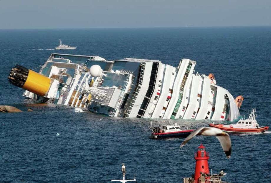 The luxury cruise ship Costa Concordia lays on its side after running aground the tiny Tuscan island of Giglio, Italy, Saturday, Jan. 14, 2012. A luxury cruise ship ran aground off the coast of Tuscany, sending water pouring in through a 160-foot (50-meter) gash in the hull and forcing the evacuation of some 4,200 people from the listing vessel early Saturday, the Italian coast guard said. (AP Photo/Gregorio Borgia) Photo: Gregorio Borgia, ASSOCIATED PRESS / AP2012
