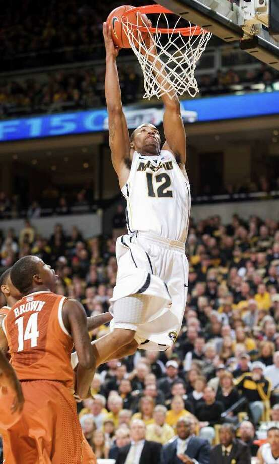 Missouri's Marcus Denmon dunks as Texas' J'Covan Brown can only watch. Denmon had 18 points and 11 rebounds in the Tigers' victory, while Brown's 34 points went for naught. Photo: ASSOCIATED PRESS, L.G. PATTERSON