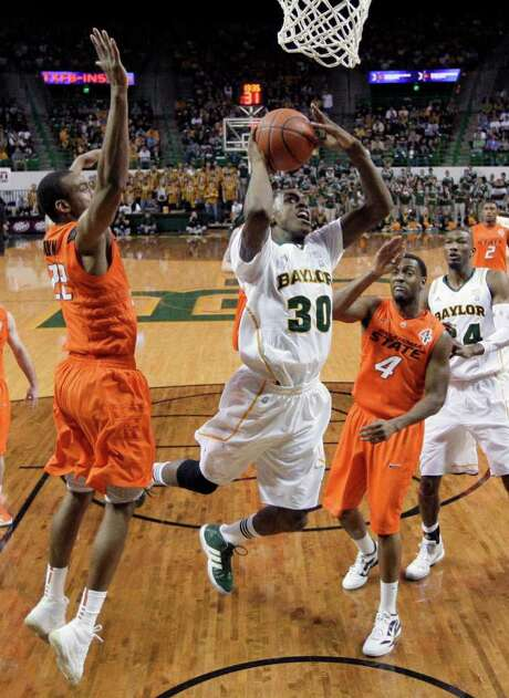 Baylor forward Quincy Miller (30) shoots between Oklahoma State 's Markel Brown (22) and Brian Williams (4) in the second half of an NCAA college basketball game Saturday, Jan. 14, 2012, in Waco, Texas. Baylor won 106-65. Photo: AP