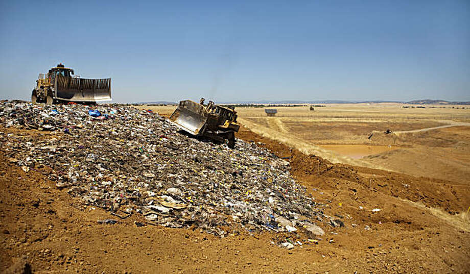 WHEATLAND, CA -- July 28, 2010. Large equipment spreads and flattens trash at the  Recology dump site, near Wheatland, California,  July 28, 2010. The city of San Francisco is considering a plan to ship all of its trash to the dump in Yuba County via rail. Some county residents, naturally, are angry that they are going to get stuck dealing with San Francisco's  trash while others say it is an economic boon for the county .  Robert Durell/For The Chronicle Photo: Robert Durell, Special To The Chronicle