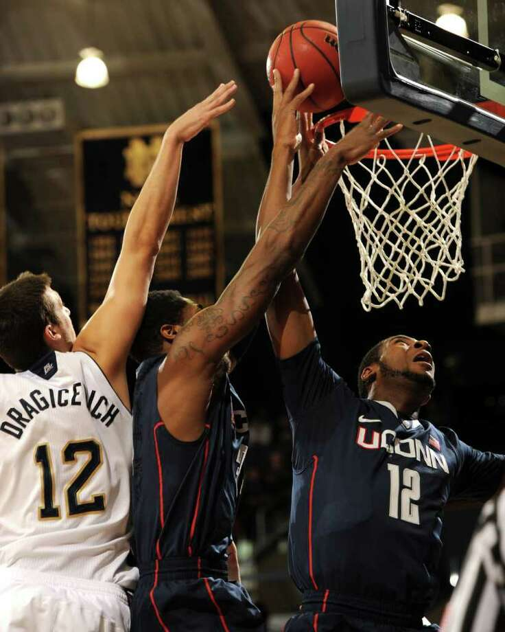 Connecticut center Andre Drummond, right, puts up a shot as Connecticut forward Alex Oriakhi assists over Notre Dame guard Alex Dragicevich in the first half of an NCAA college basketball game, Saturday, Jan. 14, 2012, in South Bend, Ind. (AP Photo/Joe Raymond) Photo: JOE RAYMOND, Joe Raymond/Associated Press / Joe R. Raymond