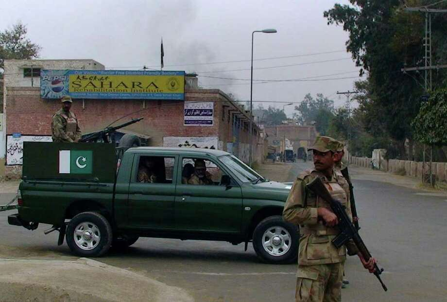 Pakistani army troops stand guard as smoke rises from a police station following the militants attack in Dera Ismail Khan, Pakistan on Saturday, Jan. 14, 2012. Gunmen and suicide bombers attacked a police station, sparking a firefight that killed three officers and one civilian, said Bahawal Khan, a local police official. The militants struck about midday Saturday in Dera Ismail Khan district and fighting continued for hours afterward. Photo: Ishtiaq Mahsud, AP / AP