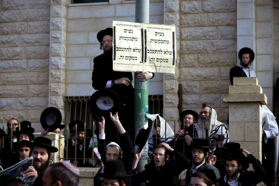 """Ultra-Orthodox Jewish men gather around a sign that reads in Hebrew: """"Women are asked not to linger in this area"""" outside a synagogue in the central Israeli town of Beit Shemesh, Monday, Dec. 26, 2011. The story of an 8-year-old American girl that has unwittingly found herself on the front line of Israel's latest religious war, drew new attention to the religious tensions in Beit Shemesh, a city of some 100,000 just outside Jerusalem, which has become a symbol of the growing violence of Jewish extremists in Israel in recent years. Photo: Oded Balilty, AP / AP"""