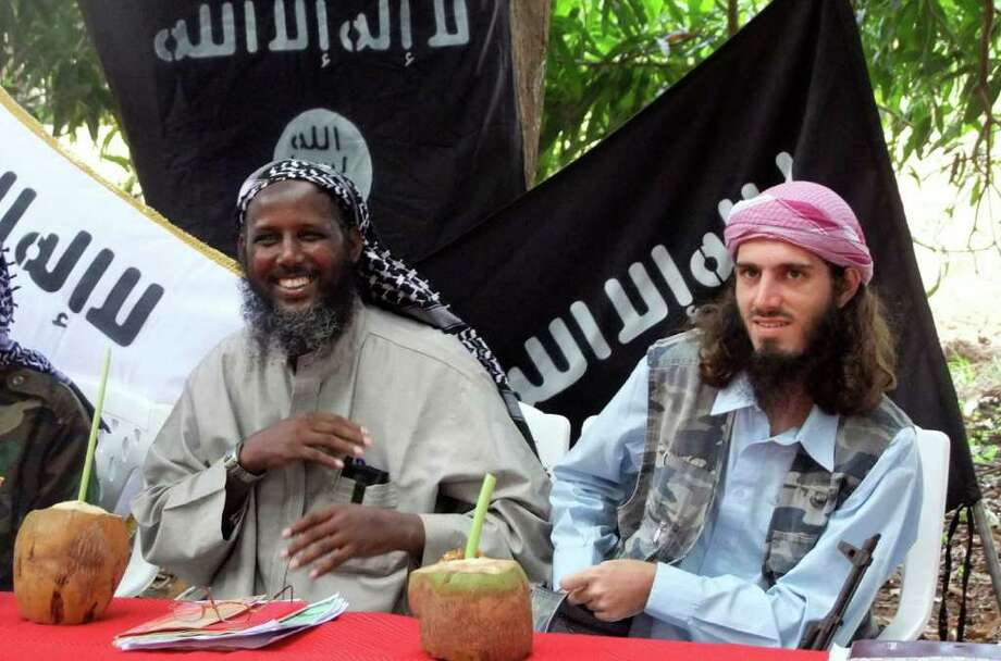 "FILE - In this Wednesday, May 11, 2011 file photo, American-born Omar Hammami, 27, also known as Abu Mansur al-Amriki, right, and deputy leader of al-Shabab Sheik Mukhtar Abu Mansur Robow, left, sit under a banner which reads ""Allah is Great"" during a news conference by the militant group at a farm in southern Mogadishu's Afgoye district in Somalia. A handful of young Muslims from America are taking high-visibility propaganda and operational roles in the al-Qaida-linked insurgent force. In the meantime, the risk of another major terrorist attack in East Africa appears to be growing. Photo: AP"