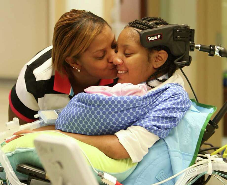 Sherry Yokum kisses her daughter, Chyna Young, at TIRR Memorial Hermann after the quadriplegic teen drove a wheelchair while holding her baby for the first time Nov. 25. Young had a healthy girl, Jada, despite her paralysis. Photo: Karen Warren / © 2011 Houston Chronicle