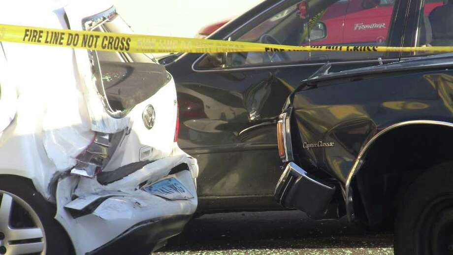 One person was hospitalized with non-life-threatening injuries after crashing a car through a North Avenue fence and into a parked car, which slammed into an auto body shop Saturday. Photo: Steve Krauchick / Connecticut Post freelance