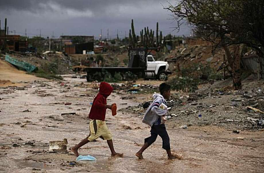 Children cross a creek bed in a poor neighborhood as Hurricane Jimena arrives in Cabo San Lucas, Mexico, Tuesday, Sept. 1, 2009. Photo: Guillermo Arias, AP